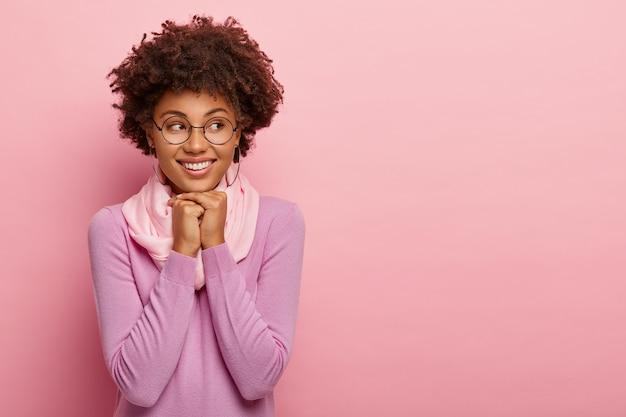 Vrolijke lachende schattige vrouw houdt beide handen onder de kin, kijkt opzij, gekleed in vrijetijdskleding, draagt een bril, geïsoleerd op roze studio achtergrond