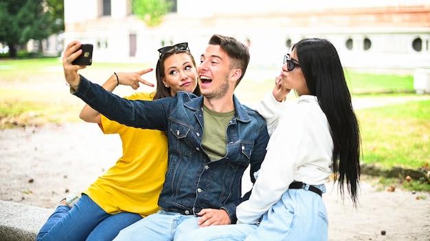 Vrolijke lachende vrienden in het park zittend op een bankje en selfies nemen met behulp van een slimme telefoon