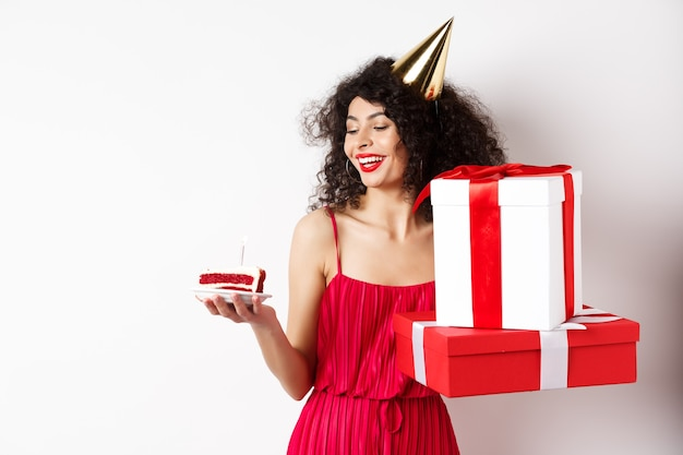 Vrolijke lachende vrouw in rode jurk en feestkegel, gelukkig kijken naar verjaardagstaart, geschenken te houden, staande op een witte achtergrond. kopieer ruimte