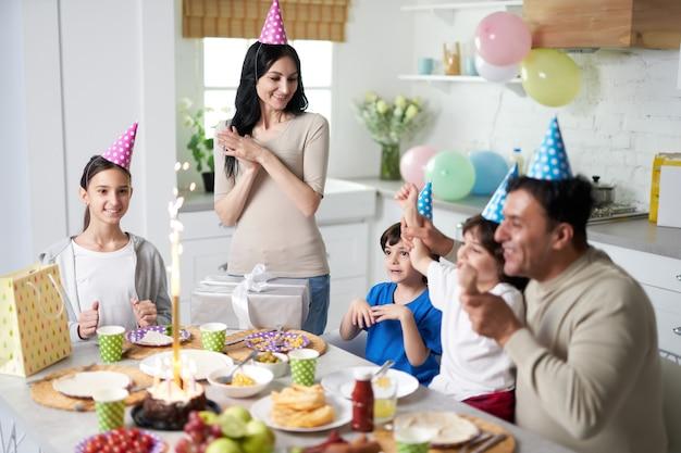 Vrolijke latijnse familie met kinderen die verjaardagspetten op hoofden dragen die er gelukkig uitzien terwijl ze thuis samen verjaardag vieren. ouderschap, vieringsconcept