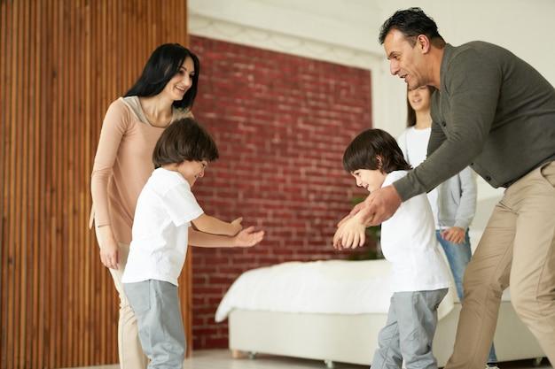 Vrolijke latijnse kinderen, kleine tweelingjongens die glimlachen terwijl ze plezier hebben met hun zus en ouders