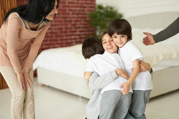 Vrolijke latijnse kinderen, tienermeisje en twee kleine tweelingjongens die elkaar knuffelen terwijl ze binnenshuis plezier hebben. pappa en mamma spelen met hun kinderen thuis. familie, kindertijd concept