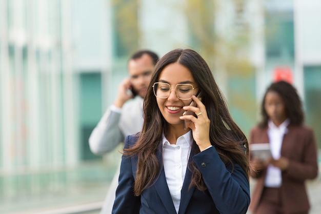 Vrolijke latijnse onderneemster met telefoon die stadsstraat daalt