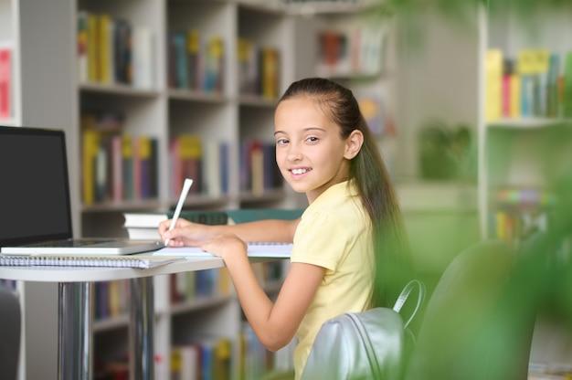 Vrolijke leerling die in haar notitieboekje schrijft