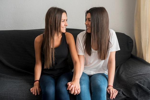 Vrolijke lesbische paar zittend op de bank