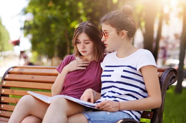 Vrolijke, leuke meisjes kijken door het laatste nummer van het lokale tijdschrift