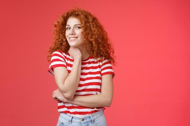 Vrolijke levendige schattige tedere roodharige krullend meisje romantische zomer stemming nadenken wat huidige vriendin gelukkige trots maand dwaze lachende aanraking gezicht-lijn kijken nieuwsgierig camera rode achtergrond.