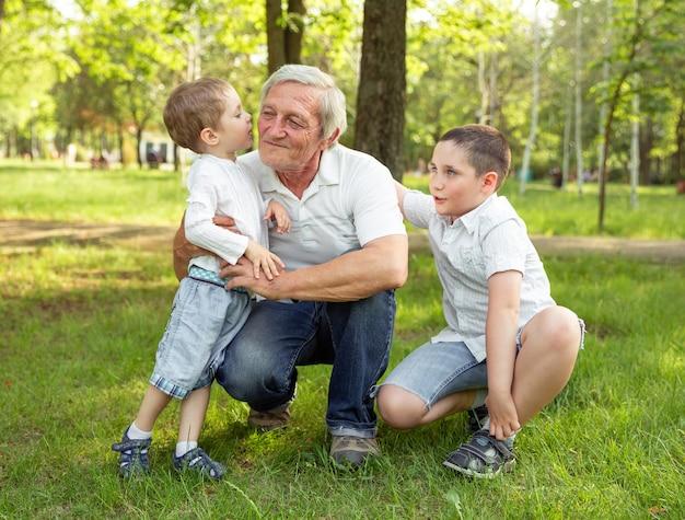 Vrolijke, liefdevolle kleinzonen die zijn grootvader knuffelen en kussen. leven