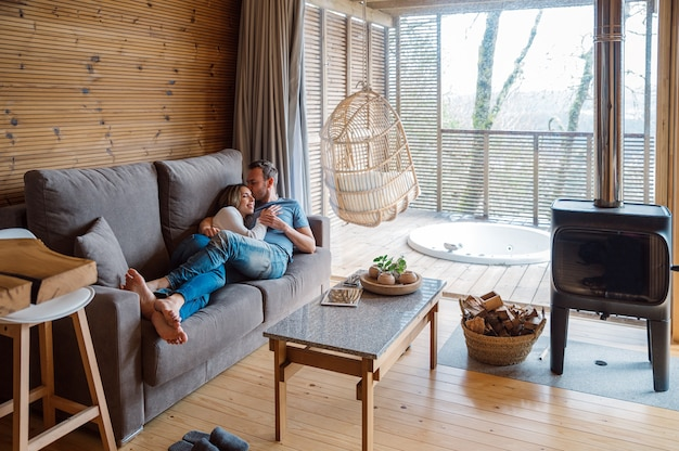 Vrolijke liefdevolle paar in casual kleding knuffelen en zoenen tijdens het rusten samen op de bank in een stijlvolle woonkamer met houten interieur