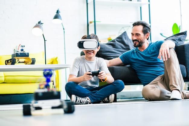 Vrolijke liefdevolle vader zit met zijn zoon die een afstandsbediening gebruikt om slimme robot te testen