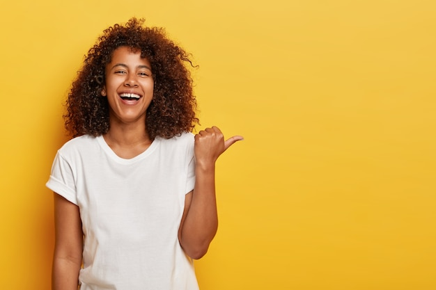 Vrolijke, lieftallige meid wijst met de duim naar de zijkant, lacht vrolijk, heeft een stralende glimlach, toont iets cools, voelt zich geamuseerd, is in een hoge geest, draagt een wit t-shirt, poseert tegen de gele muur