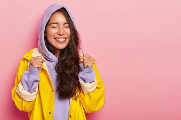 Vrolijke, lieftallige vrouw steekt gebalde vuisten op, verheugt zich op geweldige wandeling met vriendje tijdens herfstdag, gekleed in violet sweatshirt met capuchon en gele regenjas