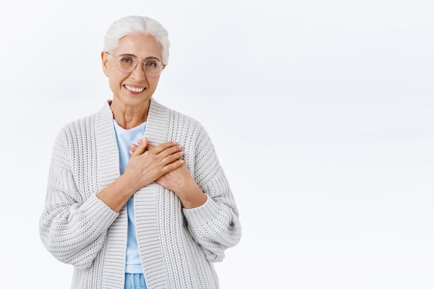 Vrolijke lieve grootmoeder, senior dame met grijs haar en rimpels, kijk aangeraakt en opgetogen, raak hart dankbaar, glimlachend waardeer nieuwjaarsverrassing