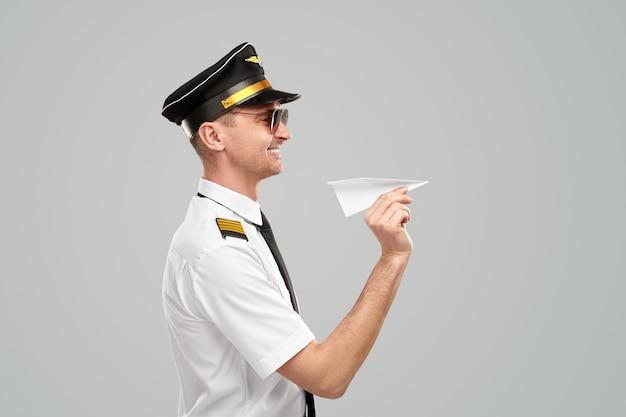 Vrolijke luchtvaartmaatschappij man piloot met papieren vliegtuigje