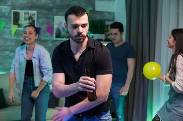 Vrolijke man die een bierflesje vasthoudt terwijl hij danst met zijn vrienden op een feestje in zijn huis.