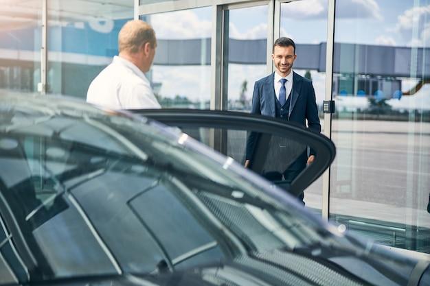 Vrolijke man die glimlachend het vliegveld verlaat en wordt opgewacht door een taxichauffeur die naast de auto staat