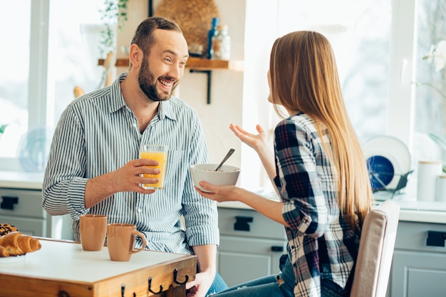 Vrolijke man die lacht naar een jonge dame terwijl hij ontbijt met haar in de keuken