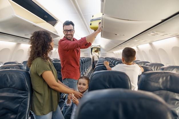 Vrolijke man die met een glimlach naar zijn vrouw kijkt en bagage in het compartiment zet terwijl hij samen met zijn gezin per vliegtuig reist. familievakantie, vervoersconcept