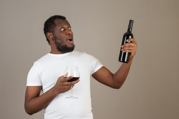 Vrolijke man die naar de wijnfles in zijn hand kijkt, staande voor de grijze muur