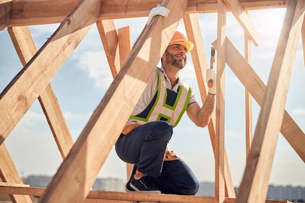 Vrolijke man die op één knie staat en een spijker slaat met een hamer terwijl hij een houten dakkarkas bouwt