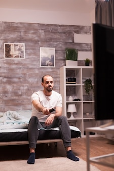 Vrolijke man die 's nachts naar een tv-show kijkt in een pyjama.