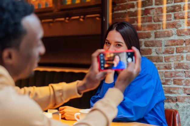 Vrolijke man die selfie maakt met zijn vriendin in café