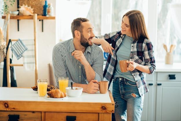Vrolijke man die van thee geniet en een glimlachende vrouw die een elleboog op zijn schouder legt