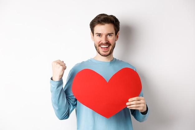 Vrolijke man die vastbesloten is om liefde te vinden op valentijnsdag, een vuistgebaar maakt en een groot rood romantisch hart vasthoudt, staande op een witte achtergrond