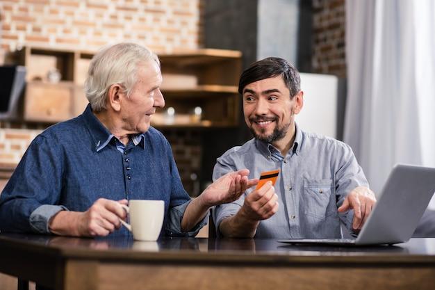Vrolijke man die zijn bejaarde vader online bankdiensten toont terwijl hij aan tafel zit