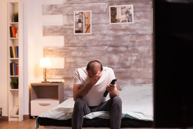 Vrolijke man die zijn gezicht bedekt terwijl hij 's nachts naar een tv-show kijkt.