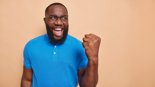 Vrolijke man doet winnaar gebaar viert overwinning maakt eerste bult roept van geluk draagt ronde bril basic blauw t-shirt geïsoleerd over beige muur