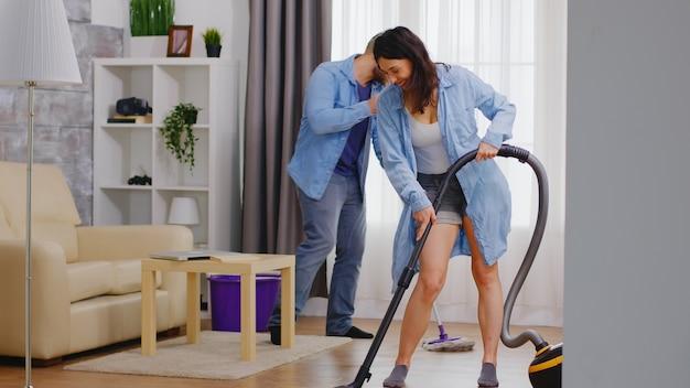 Vrolijke man en vrouw dansen en maken het huis schoon