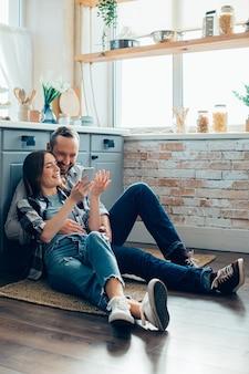 Vrolijke man en vrouw die op de keukenvloer liggen en naar het smartphonescherm kijken