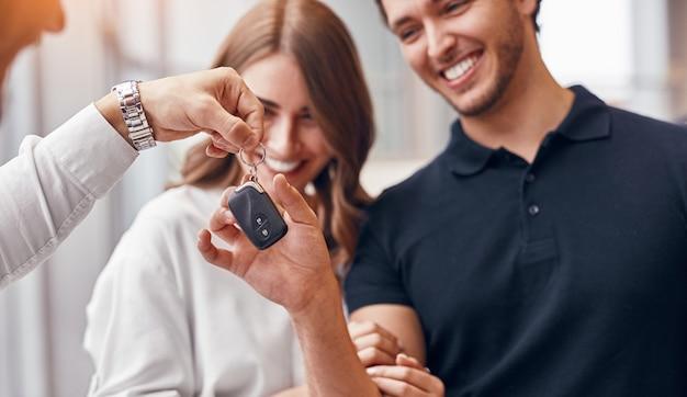 Vrolijke man en vrouw glimlachen en het nemen van sleutels van dealer tijdens het kopen van een voertuig in de moderne showroom