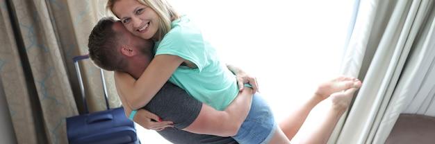 Vrolijke man en vrouw knuffelen in hotelkamer