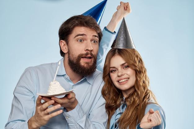 Vrolijke man en vrouw met cake in een bord bedrijfsfeestblauw