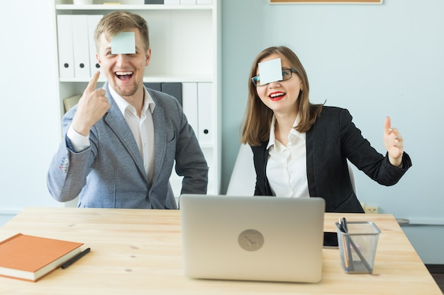 Vrolijke man en vrouw spelen tijdens het werken op kantoor.
