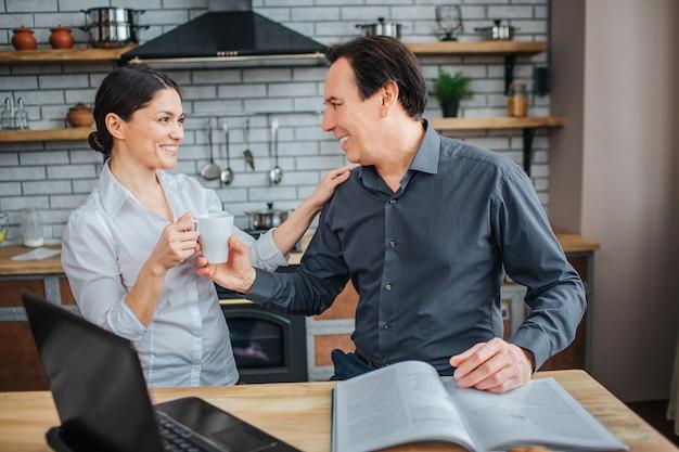 Vrolijke man en vrouw zijn samen in de keuken.