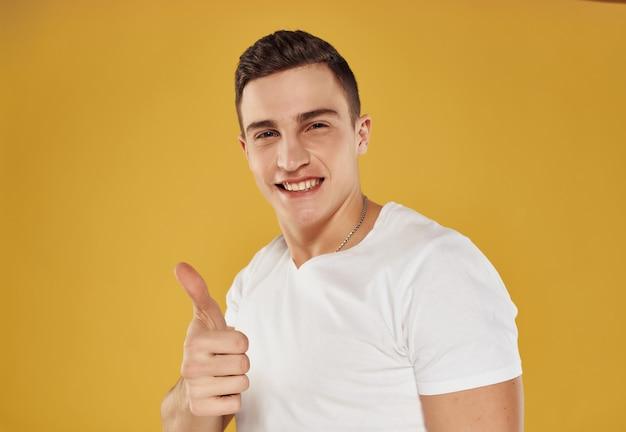 Vrolijke man gebaren met handen in witte tshirt bijgesneden weergave geïsoleerde achtergrond view