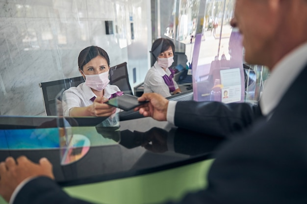 Vrolijke man geeft vrouwen documenten met steriele maskers om in te checken voor de vlucht op de luchthaven