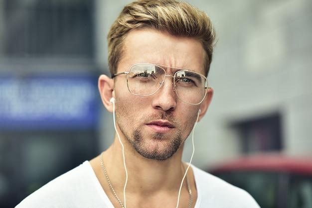 Vrolijke man gekleed in t-shirt op straat, luisterend naar muziek met koptelefoon. oortelefoon concept.