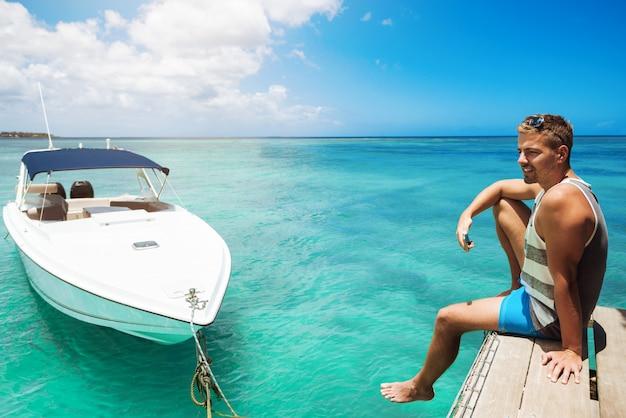 Vrolijke man genieten van de zomer op het strand met telefoon wegkijken