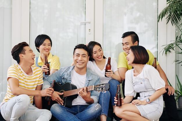 Vrolijke man gitaarspelen voor vrienden