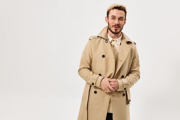 Vrolijke man in beige jas herfststijl modieuze kapselstudio