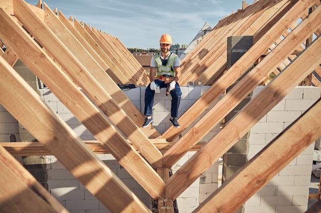 Vrolijke man in een beschermende helm en een goed zichtbaar vest met een boor terwijl hij op het dak van het gebouw zit