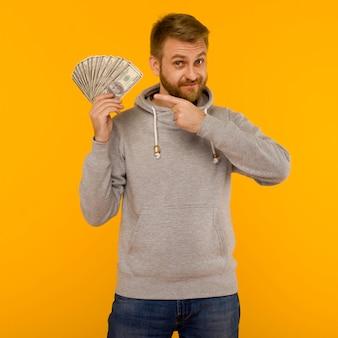 Vrolijke man in een grijze hoodie wijst met een vinger naar geld dollars op een gele achtergrond - afbeelding