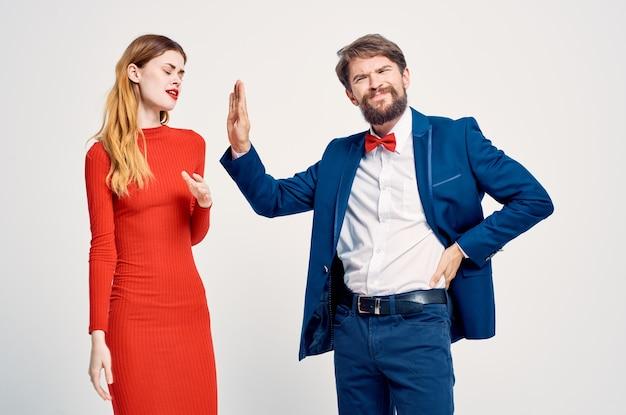 Vrolijke man in een pak naast een vrouw in een rode jurk kennis