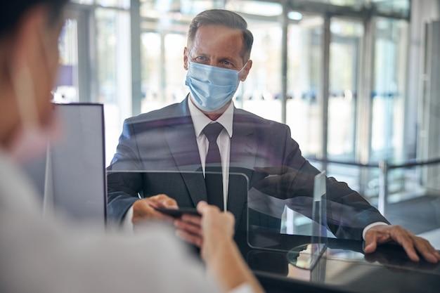 Vrolijke man in elegant pak en masker staat aan de registratiebalie en geeft documenten aan de vrouwelijke manager op de luchthaven