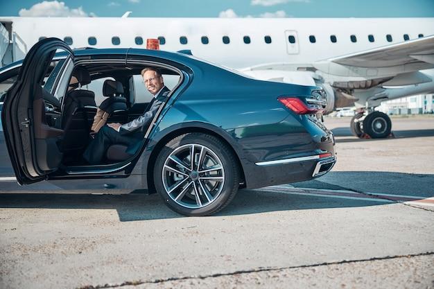 Vrolijke man in elegant pak stapt uit auto na transfer naar jet voor vertrek