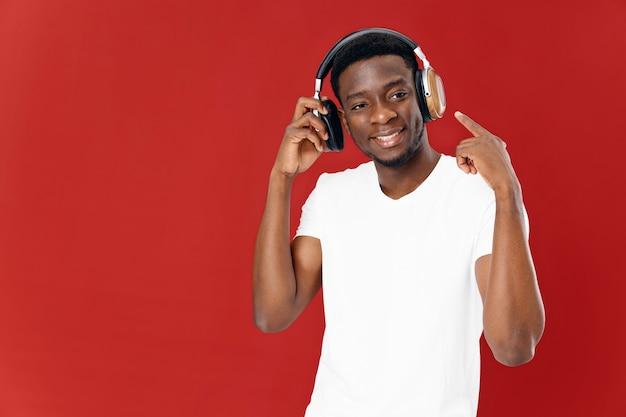 Vrolijke man in hoofdtelefoons technologie muziekliefhebber rode achtergrond